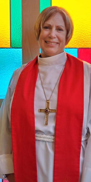 Bishop Joy in front of stained glass at her installation